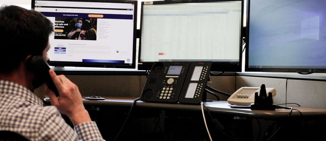 Photo of a man on the phone with the coronavirus website on his computer screen